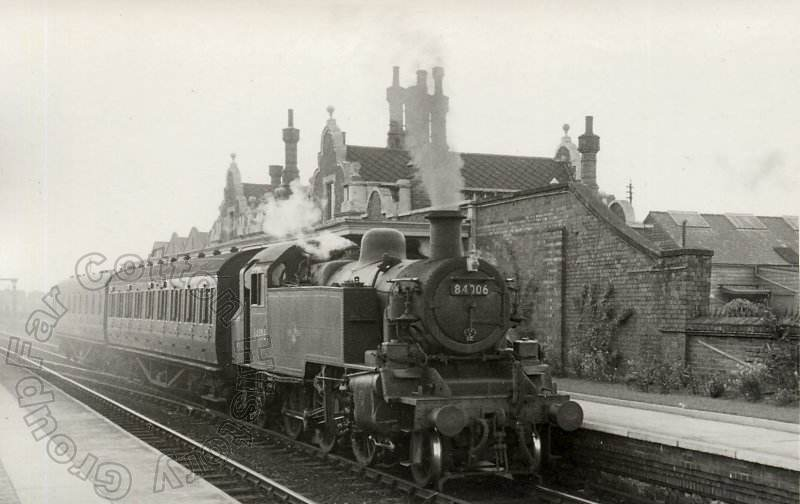 Standard Class 2MT 2-6-2T no. 84006 passes Northampton Bridge Street Station with the 4:24pm train from Northampton Castle to Wellingborough Midland Road. 29 April 1959. Courtesy Robin Puryer